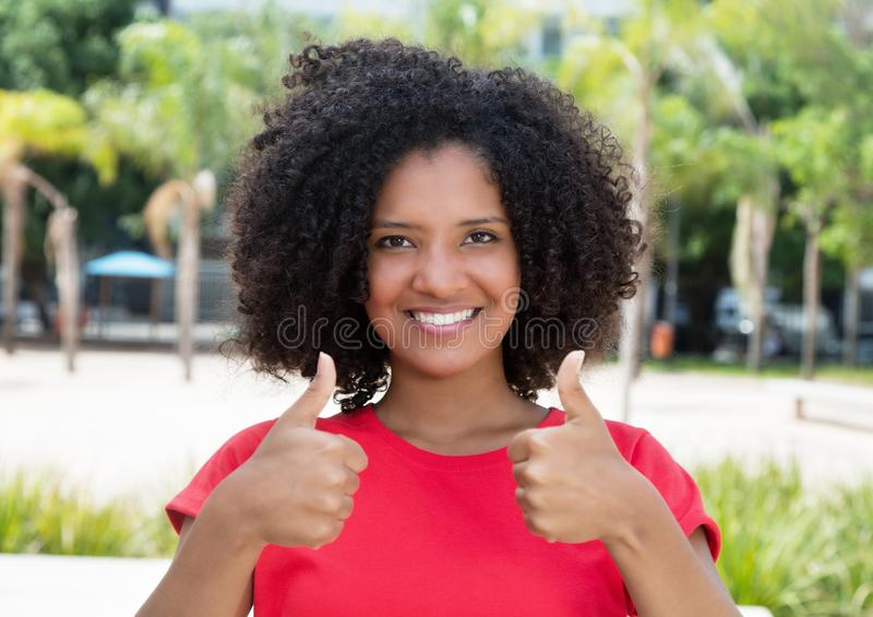 Teenager afroamericano in camicia rossa che mostra entrambi i pollici su fotografie stock