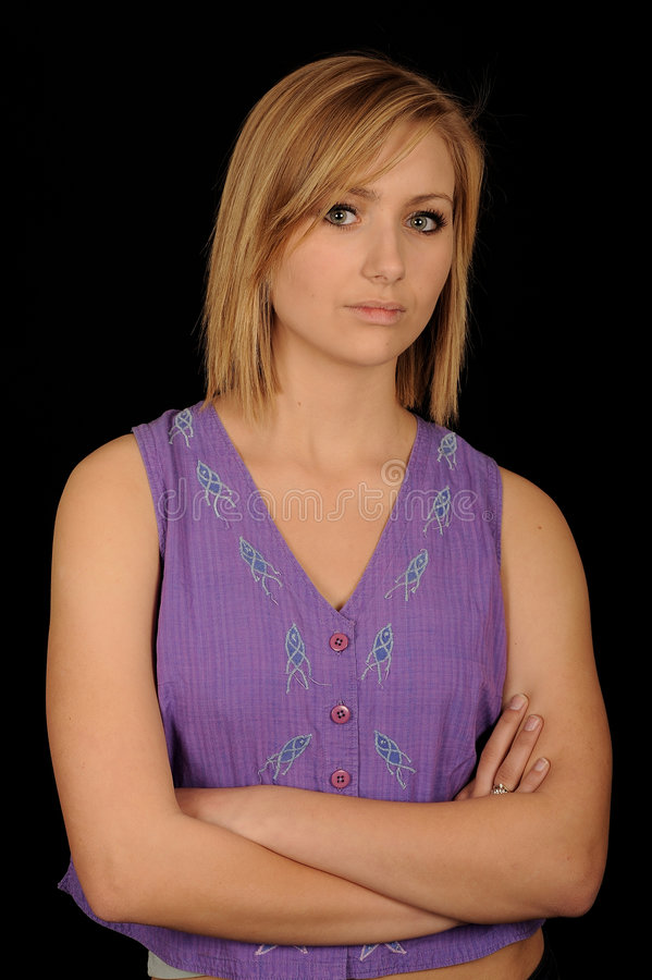 Teenager with arms folded. Half body portrait of pretty blond teenager with arms folded, black background royalty free stock photos