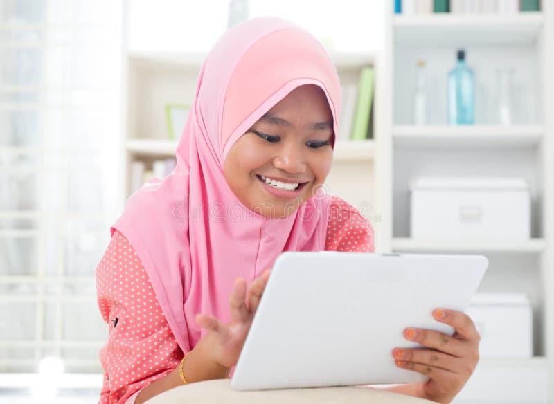 Teenager asiatico facendo uso del computer del pc della compressa. fotografia stock