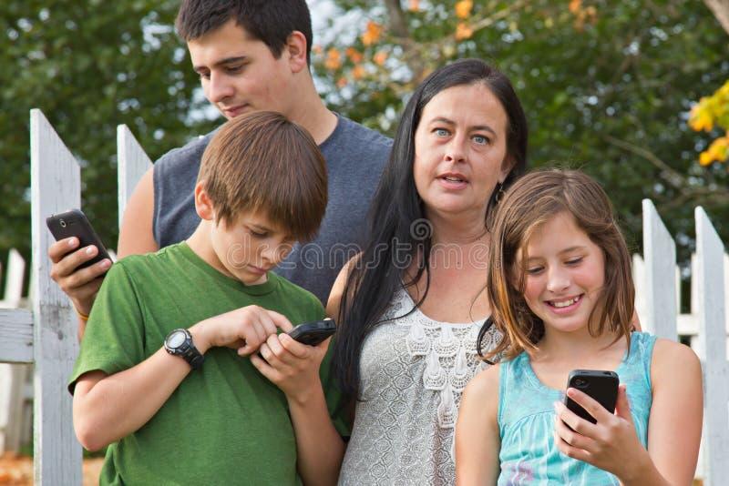 Teenager auf Mobiltelefonen stockfotografie