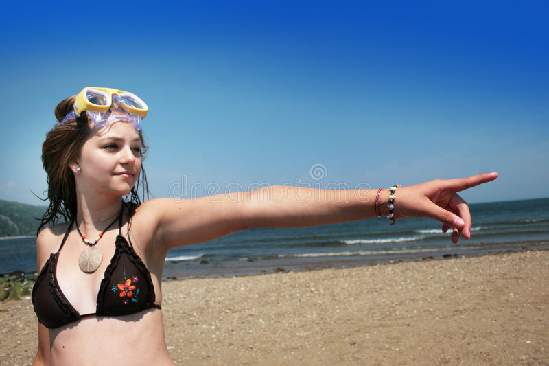 Teenager at beach pointing royalty free stock image