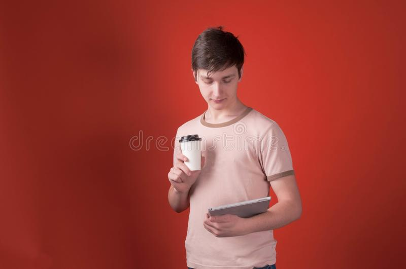 Teenager in beige t shirt standing with coffee in paper cup and looking at digital tablet royalty free stock photos