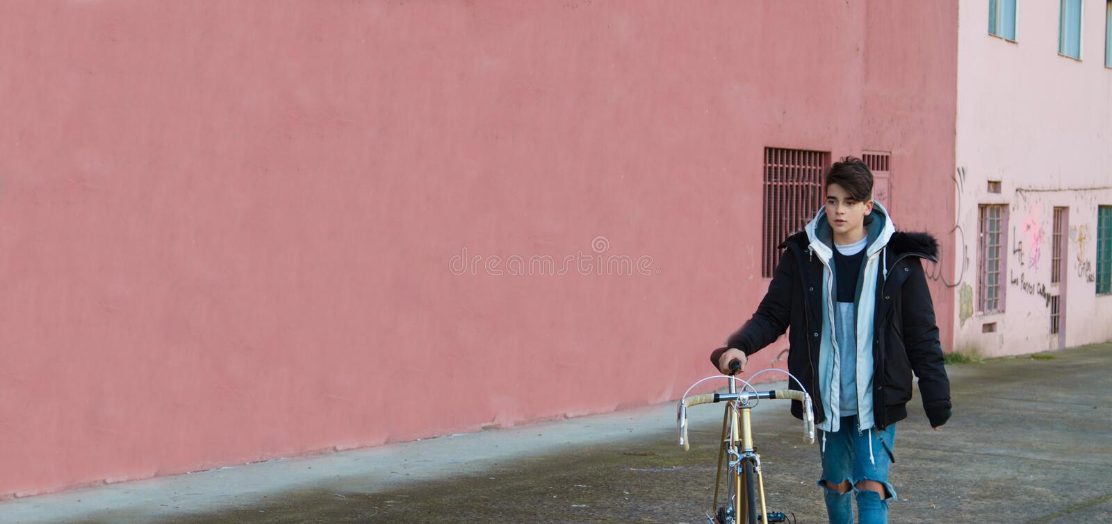 Teenager with bicycle on the street outdoors royalty free stock photography