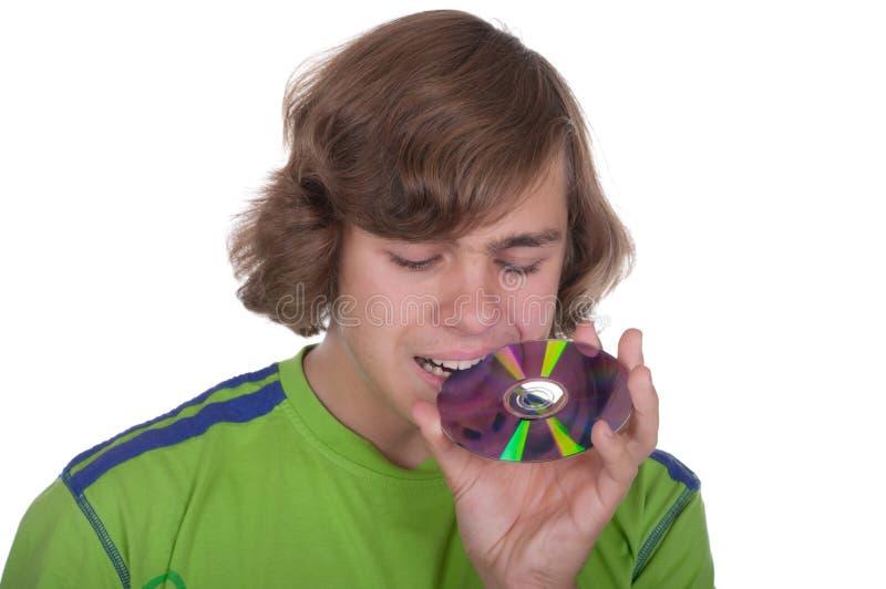 Teenager bites an optical disk stock photo