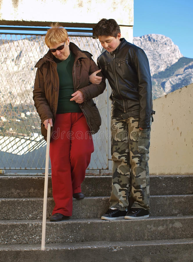 A teenager and a blind woman stock photos