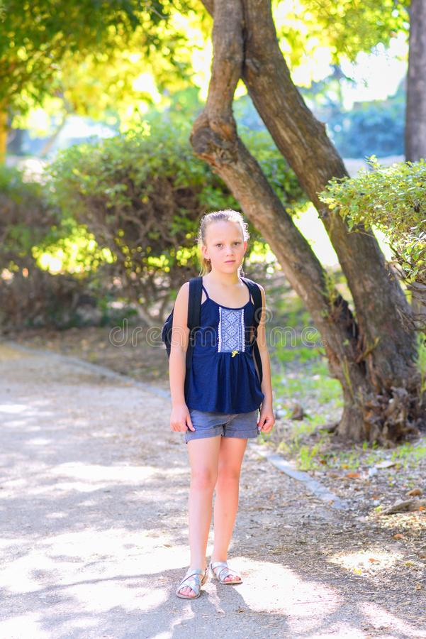Teenager blonde kid Back to school. Child little girl with bag go to elementary school. royalty free stock image