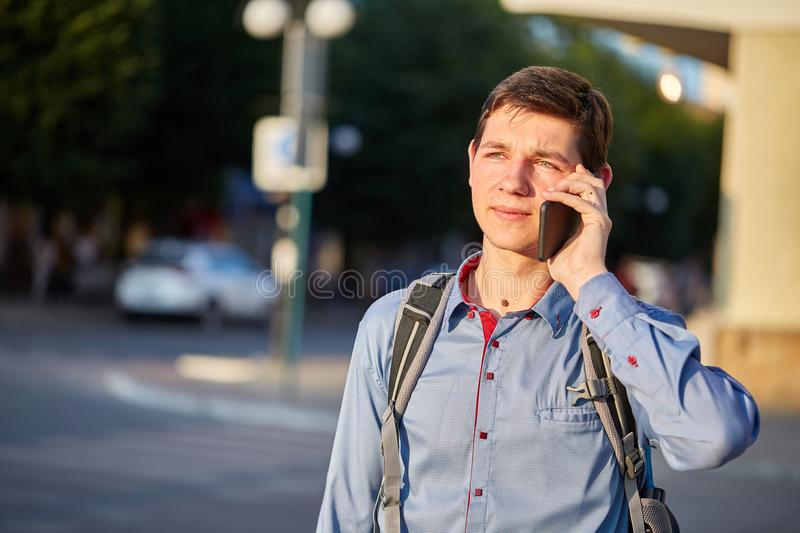 A teenager talking on his phone while walking around the city on the background of the street. stock image