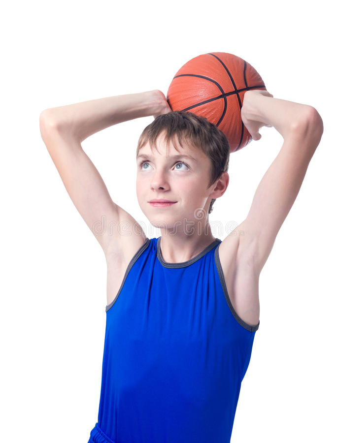 Teenager in a blue t-shirt with an orange ball for basketball over his head. Isolated on white background royalty free stock images