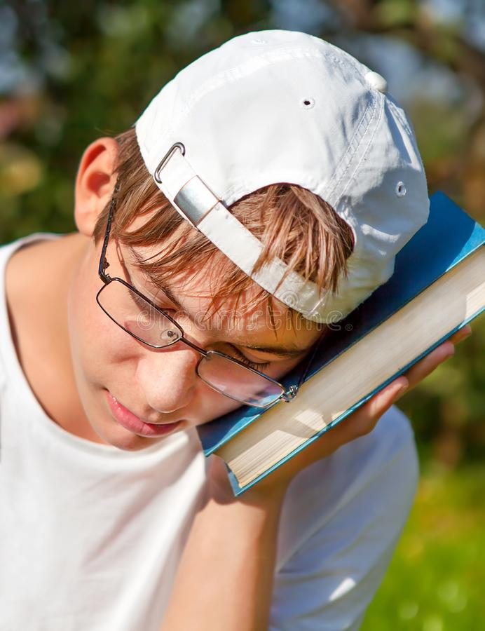 Teenager with a Book. Sad and Tired Teenager with a Book in the Summer Park stock photography