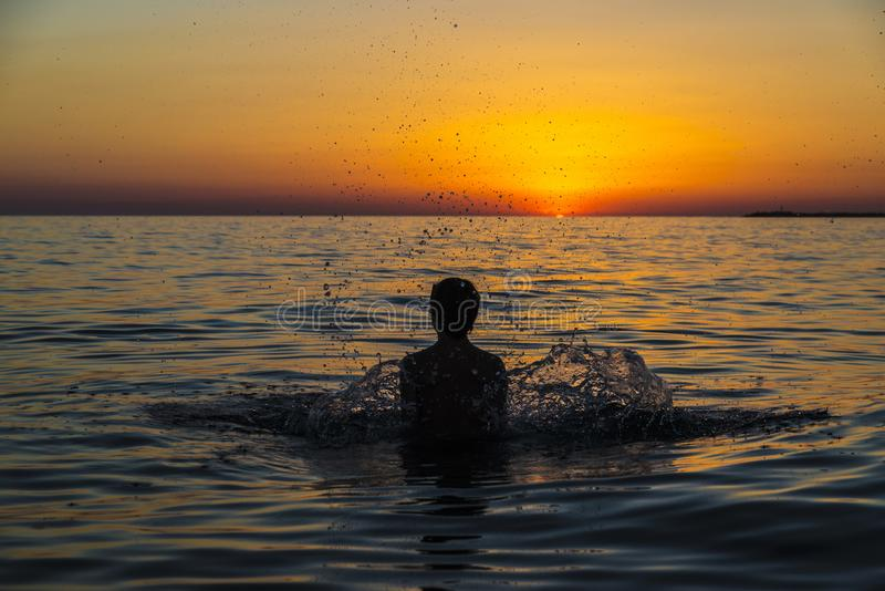 Teenager boy bathing in the sea at sunset in Sicily stock photos