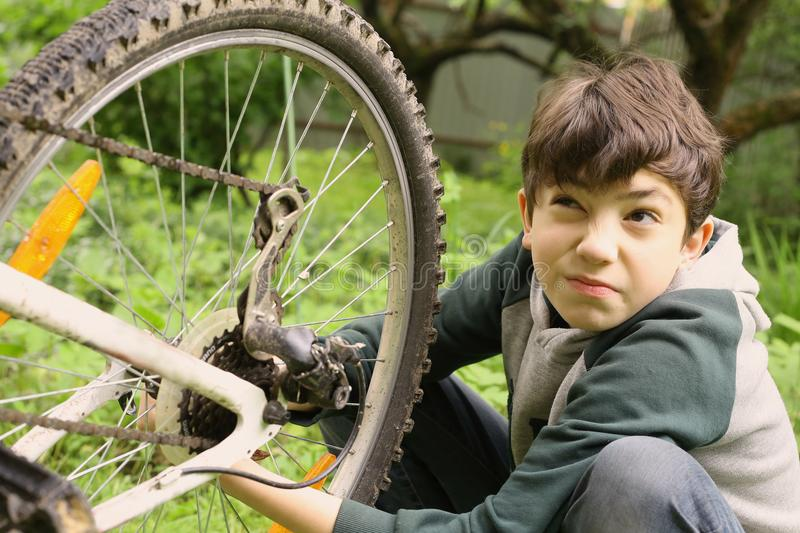 Teenager boy change bicycle tire weel camera. Close up summer green outdoor horizontal photo stock photos