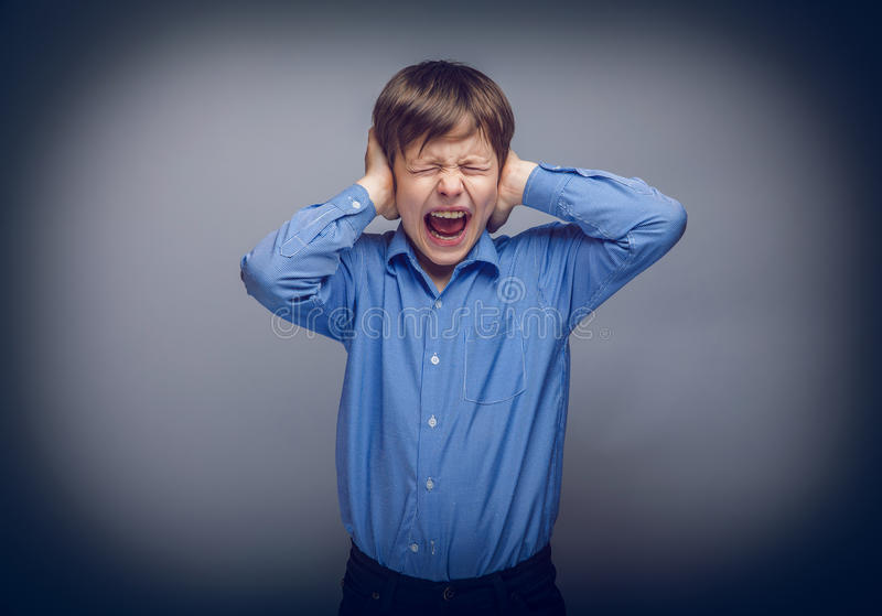 Teenager boy covering his ears screaming hands on stock photos