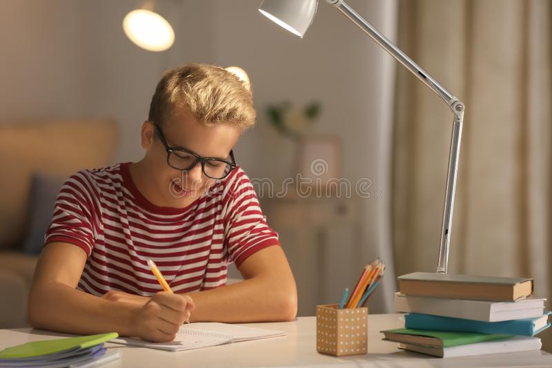 Teenager boy doing homework at home in evening stock images