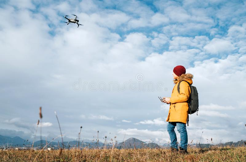 Teenager boy dressed yellow jacket piloting a modern digital drone using remote controller royalty free stock photography
