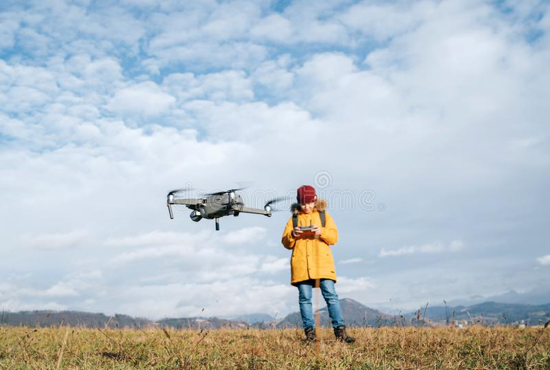 Teenager boy dressed yellow jacket piloting a modern digital drone using remote controller stock photography