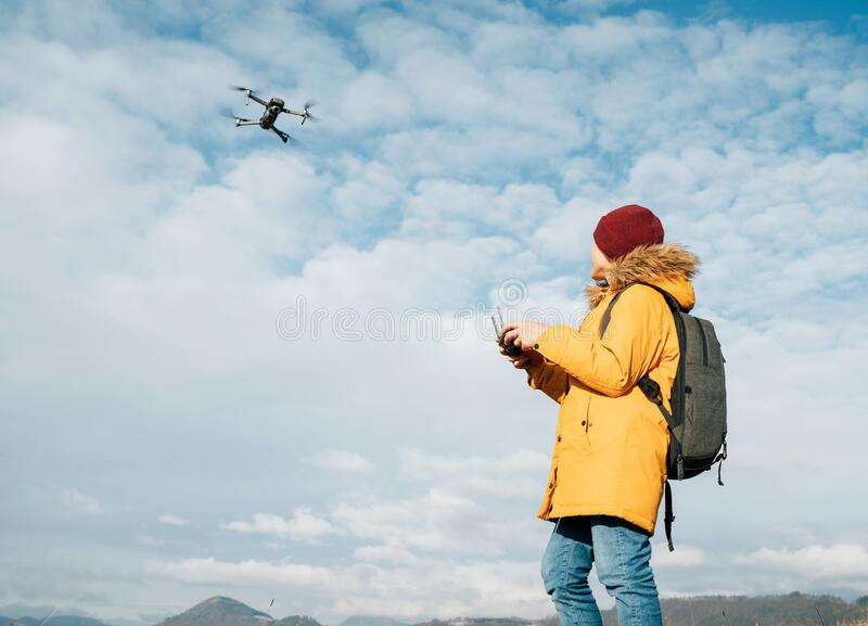Teenager boy dressed yellow jacket piloting a modern digital drone using remote controller stock photo