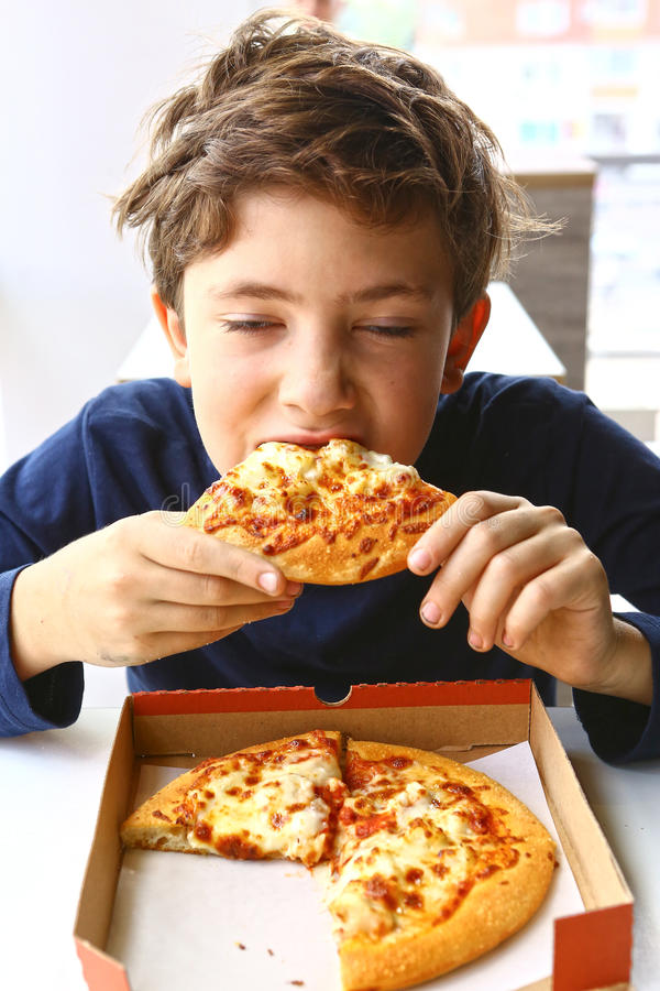 Teenager boy eat pizza in cafe. Hungry boy stock image