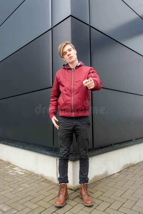 Teenager boy gesticulating and pointing at you ove urban background. Teenager boy gesticulating pointing at you posing over urban background; full length stock images