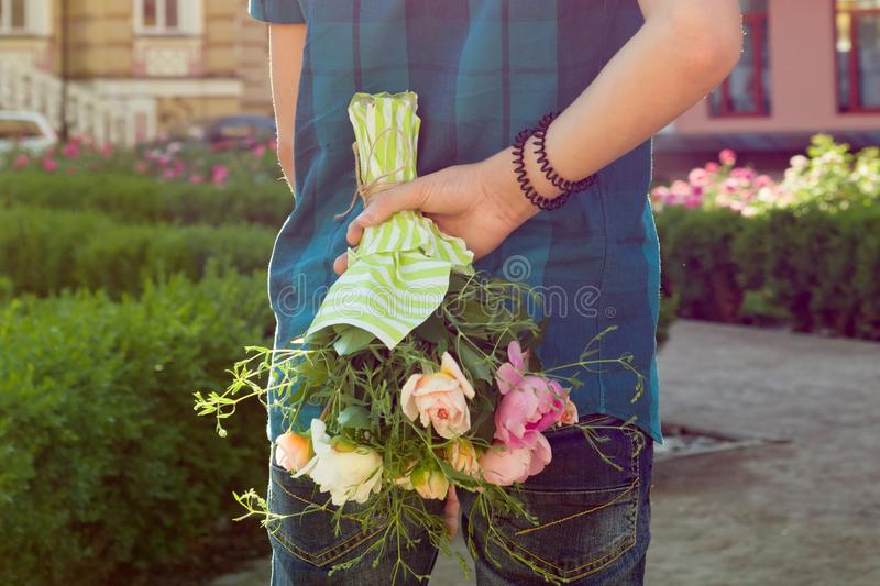Teenager boy holding bouquet of flowers behind his back. Surprise, gift, present stock photo