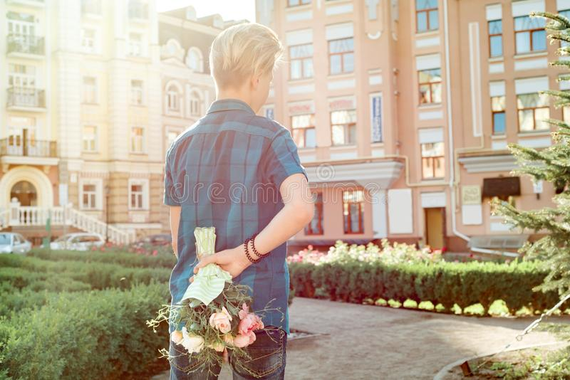 Teenager boy holding bouquet of flowers behind his back. Surprise, gift, present stock images