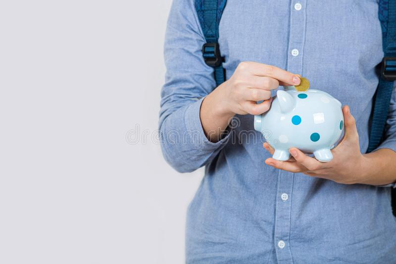 Teenager boy holding piggy bank putting euro coins inside over white background. Financial education savings concept stock photos