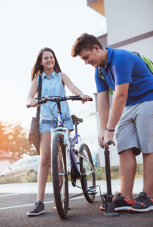 Teenager boy inflating bike tire to help his female friend. Outdoor summer photo royalty free stock images