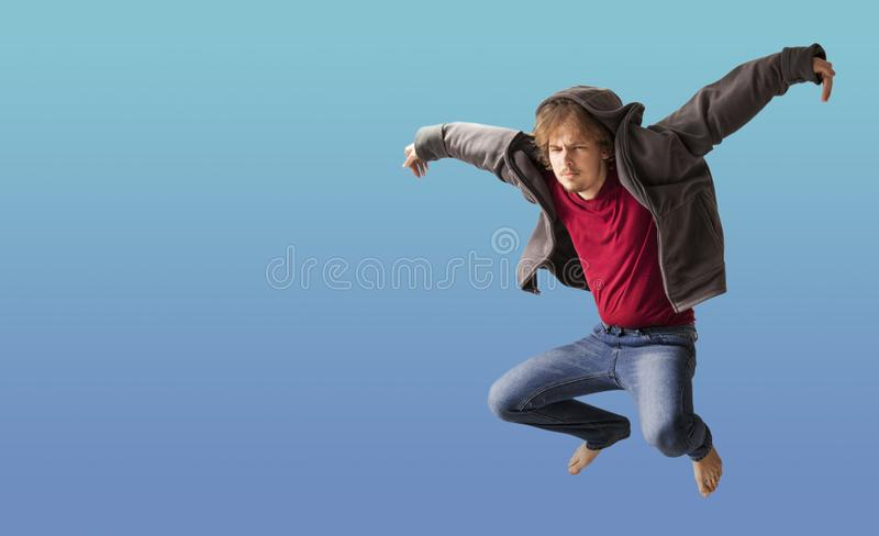 Teenager boy jumping dance movement on a colored blue background.  stock photo