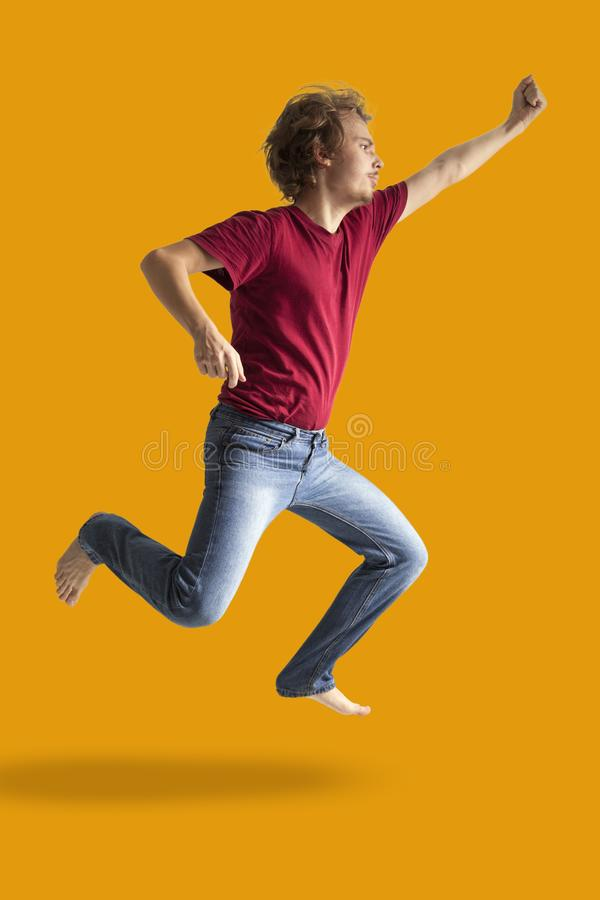 Teenager boy jumping dance movement on a colored yellow background.  royalty free stock image