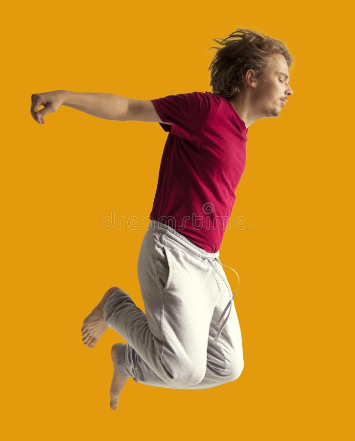 Teenager boy jumping dance movement on a colored yellow background.  royalty free stock photography