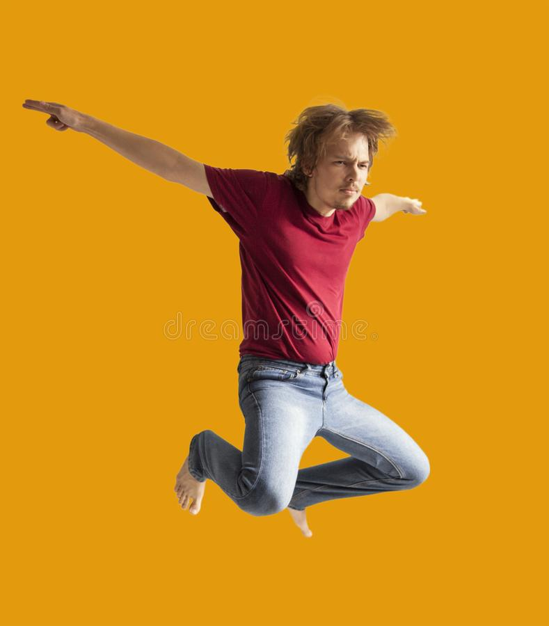 Teenager boy jumping dance movement on a colored yellow background.  stock image