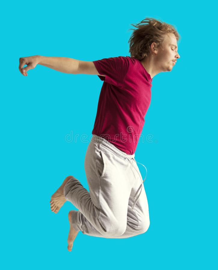 Teenager boy jumping dance movement on a colored yellow background.  royalty free stock photo