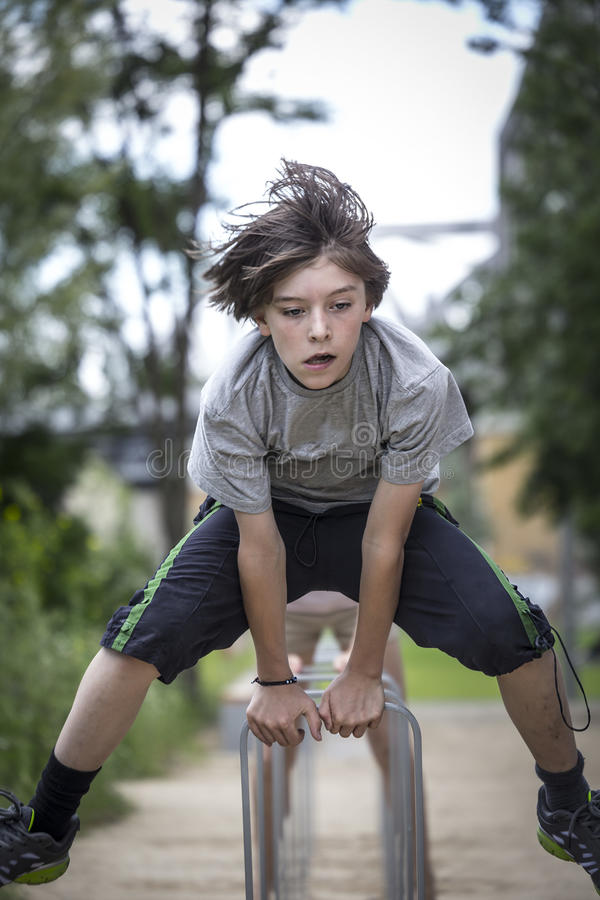 Teenager boy is jumping. Over a bike rack royalty free stock images