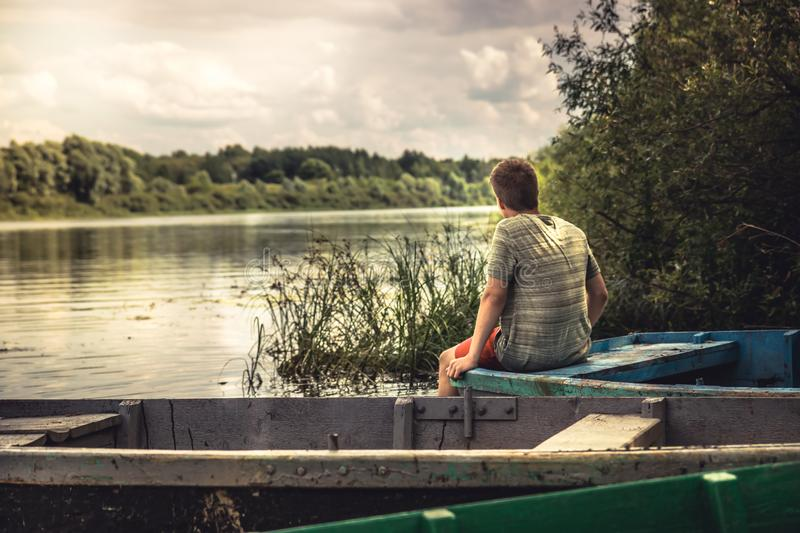 Teenager boy lonely contemplation countryside scenery on river boat during countryside summer holidays stock image