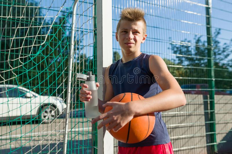 Teenager boy playing basketball with ball on the basketball court drinking water. royalty free stock photography
