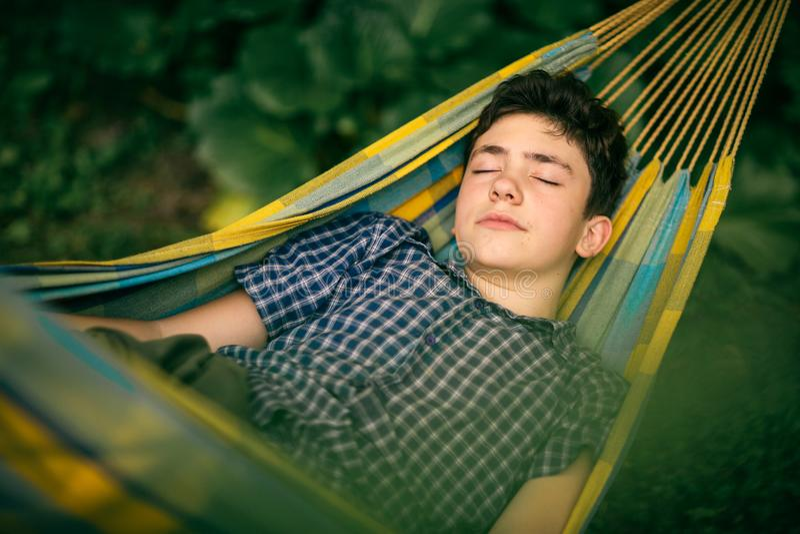 Teenager boy resting in hammock stock photos