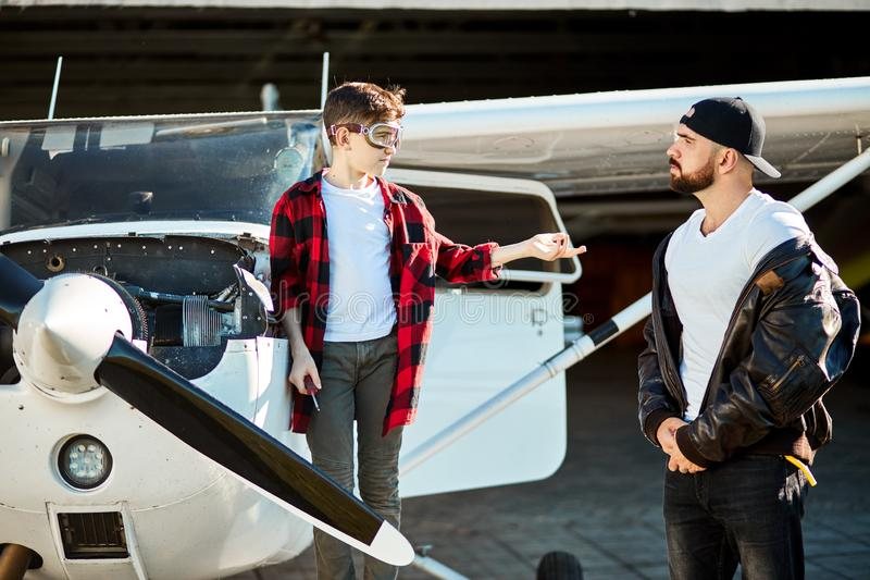 Teenager boy with screwdriver, asking for help father, standing near light plane stock image