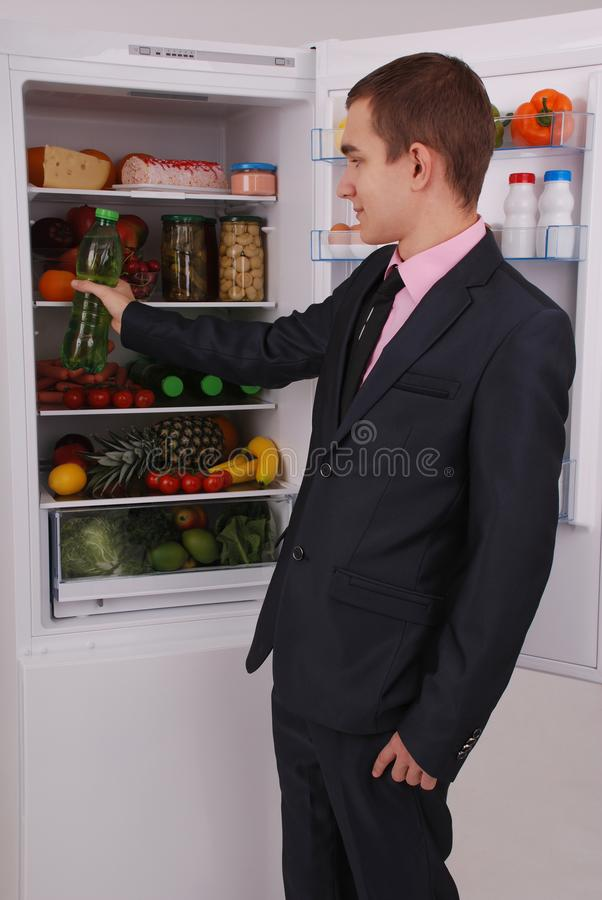Teenager boy in suit and tie near the refrigerator royalty free stock photography