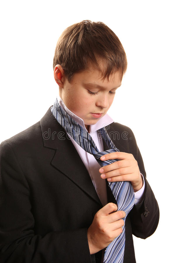 Teenager boy ties a tie on a white background stock images