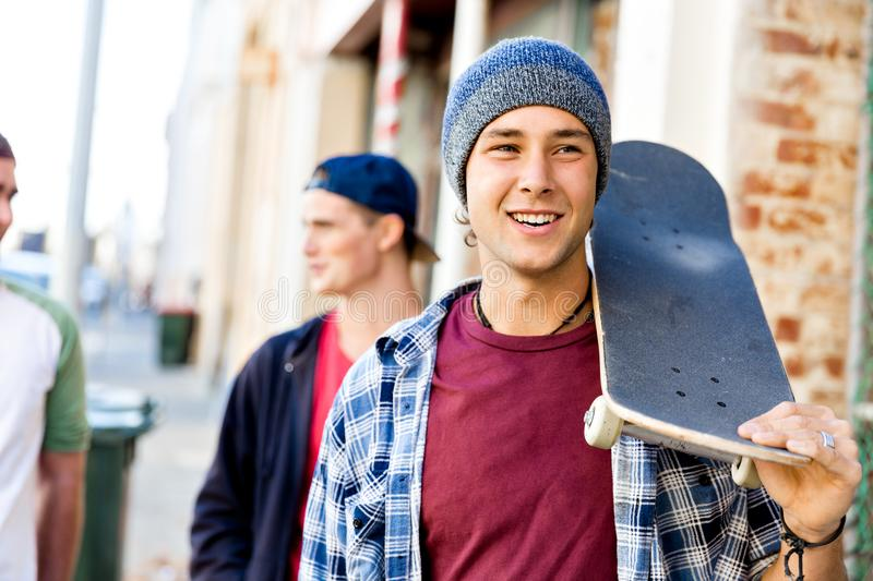 Teenager boy walking at the street with his skateboard. Teenage boy walking down the street in summer with his skateboard stock photos