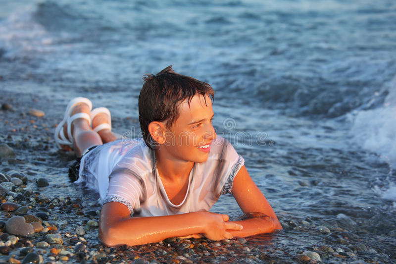 Teenager boy in wet clothes lying on seacoast stock image
