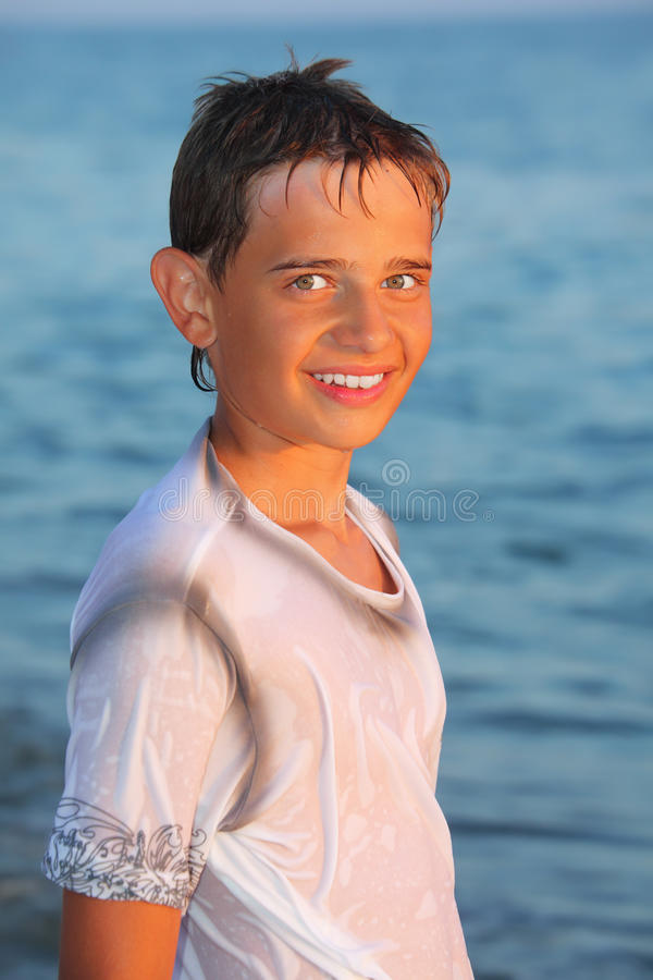 Teenager boy in wet clothes on seacoast royalty free stock photos