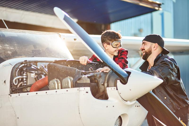 Boy dreams to be aircraft engineer, standing near white propeller plane with dad royalty free stock photos