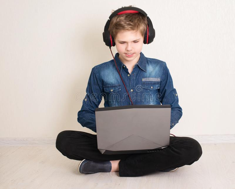 Teenager boy working on laptop computer while sitting on the floor with legs crossed with headphones on his head.  royalty free stock photography
