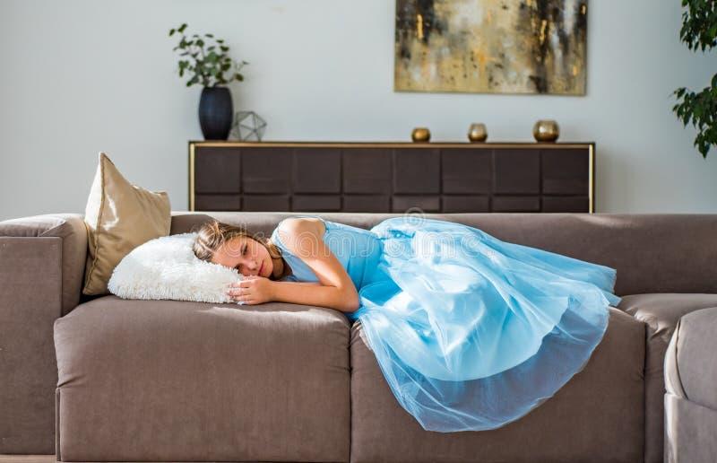 Teenager brunette girl with long hair lying on sofa at home. Young teenager brunette girl with long hair lying on sofa at home stock photo