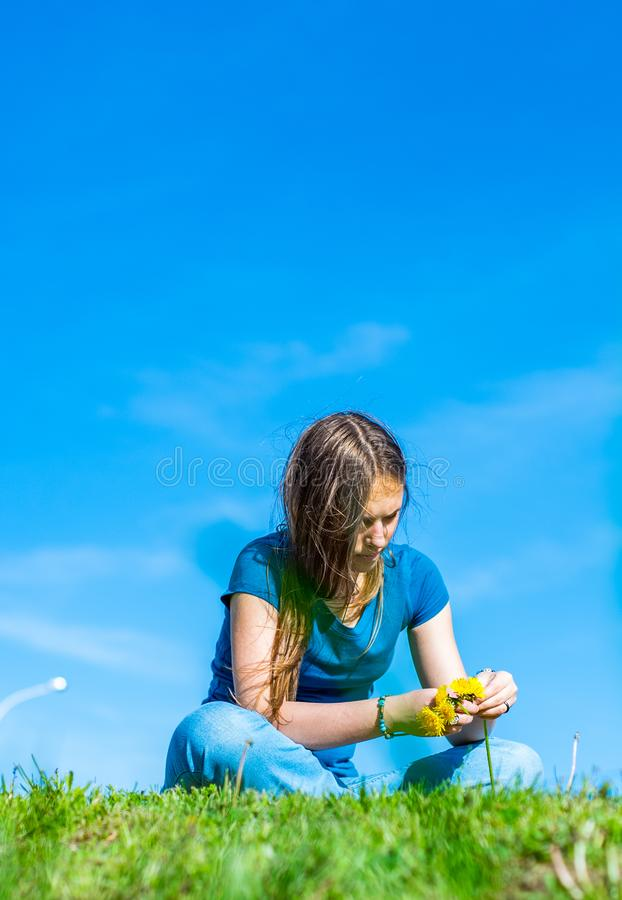 Teenager brunette girl with long hair sit on the grass and wreathes a wreath of yellow dandelion flowers on sky background with co stock photos