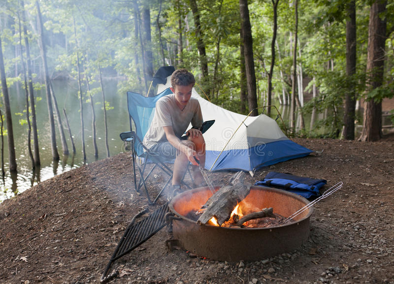 Teenager camping with camp fire. Teenager at campsite with tent and camp fire royalty free stock images
