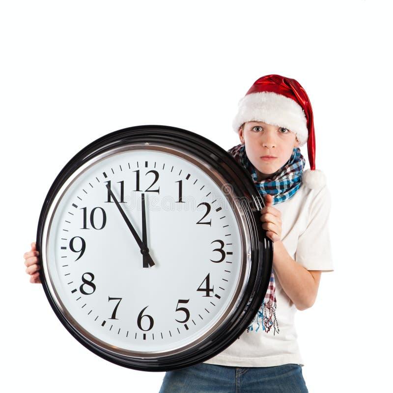 Teenager in cap of Santa Claus and large clock