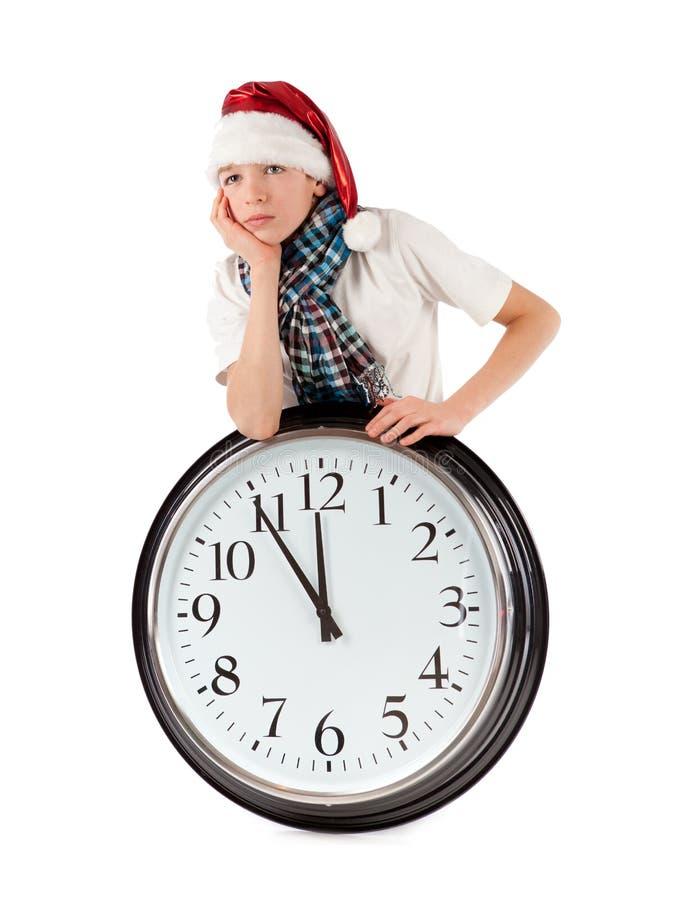 Teenager In Cap Of Santa Claus And Large Clock Stock Photos