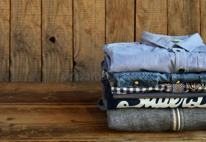 Teenager casual outfit. Boys shoes, clothing and accessories on wooden background - sweater, shirt. Top view. Flat lay stock photos
