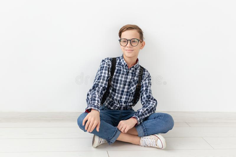 Teenager, children and fashion concept - Cute child with glasses sitting on the floor over white background stock image